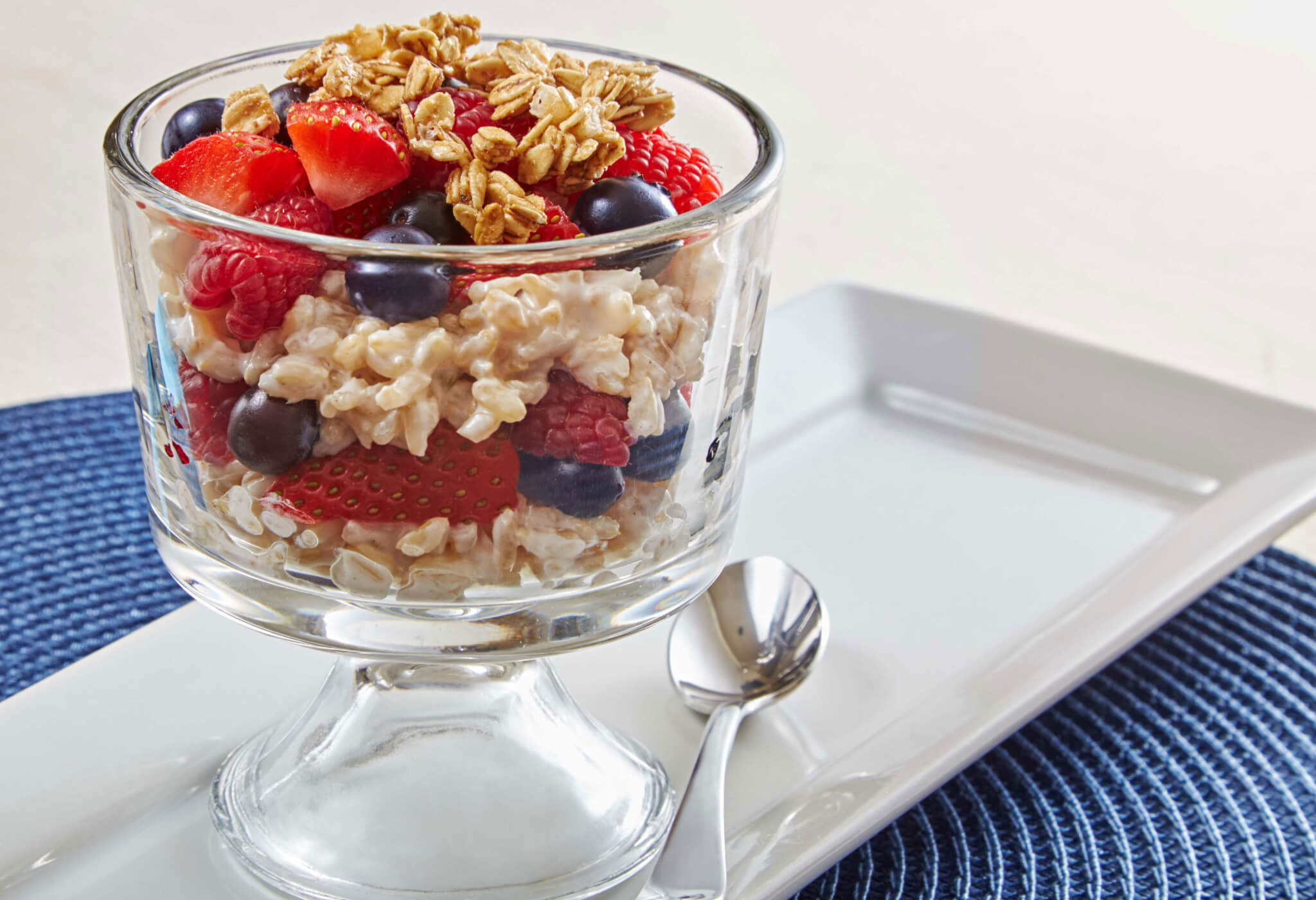 A tall glass of creamy rice layered with berries and topped with granola