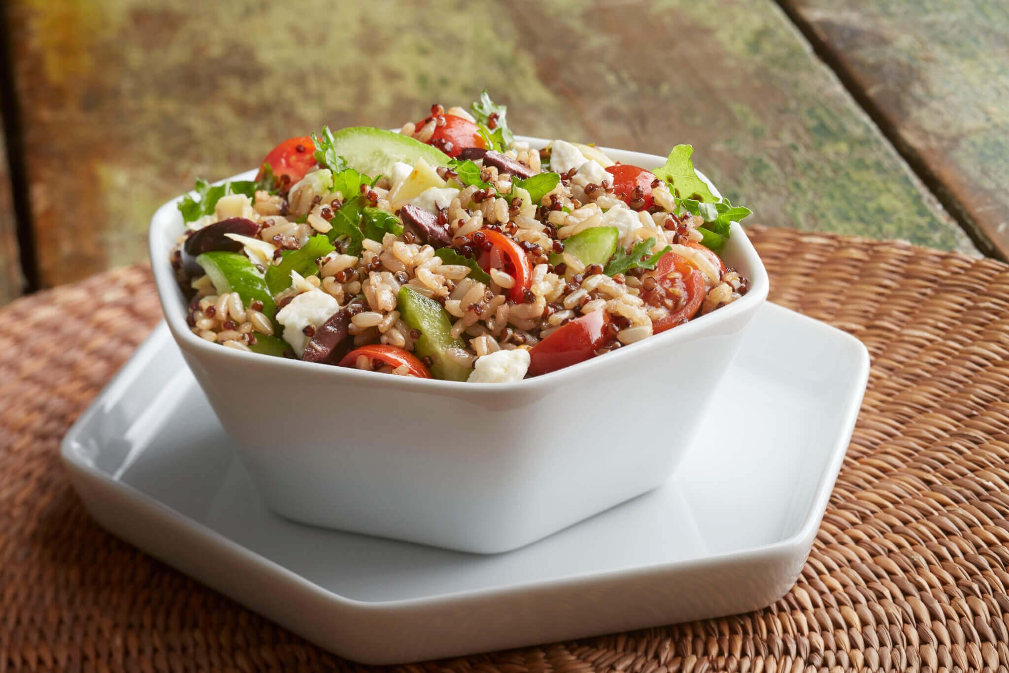 A small salad bowl filled with quinoa, chopped lettuce, cucumber, tomatoes, olives and feta cheese