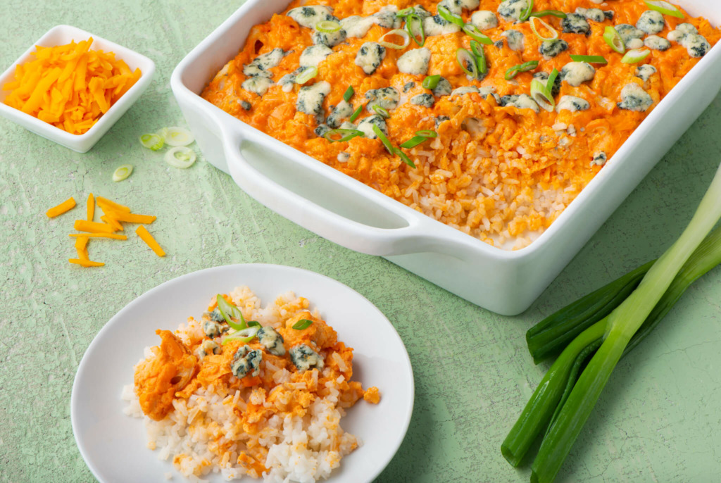 Tray of buffalo cauliflower casserole dip with rice, blue cheese and a small plate
